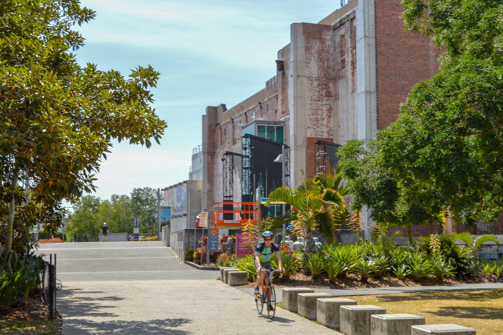 Cyclist riding past Brisbane Powerhouse in New Farm