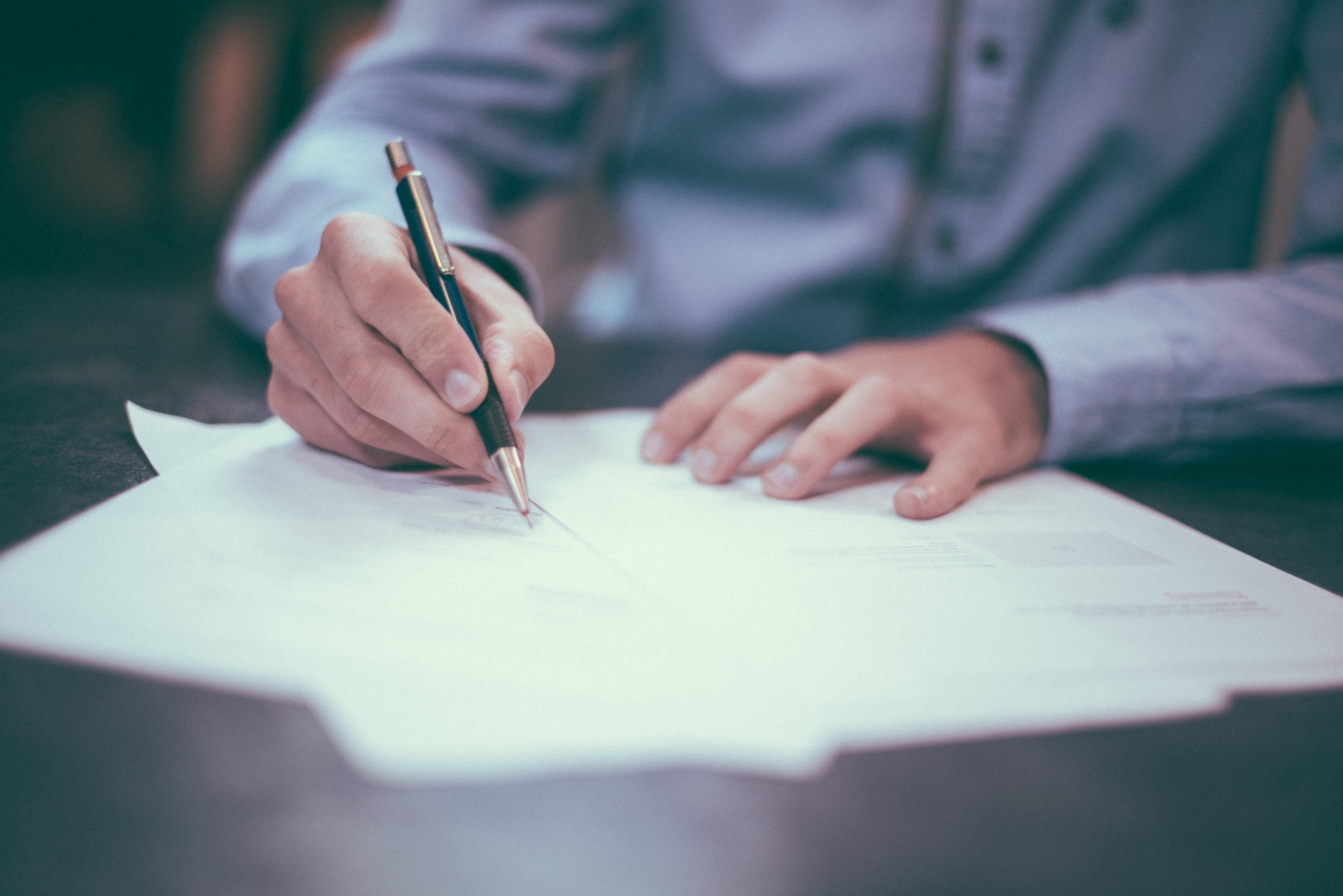 adult man signing a range of papers