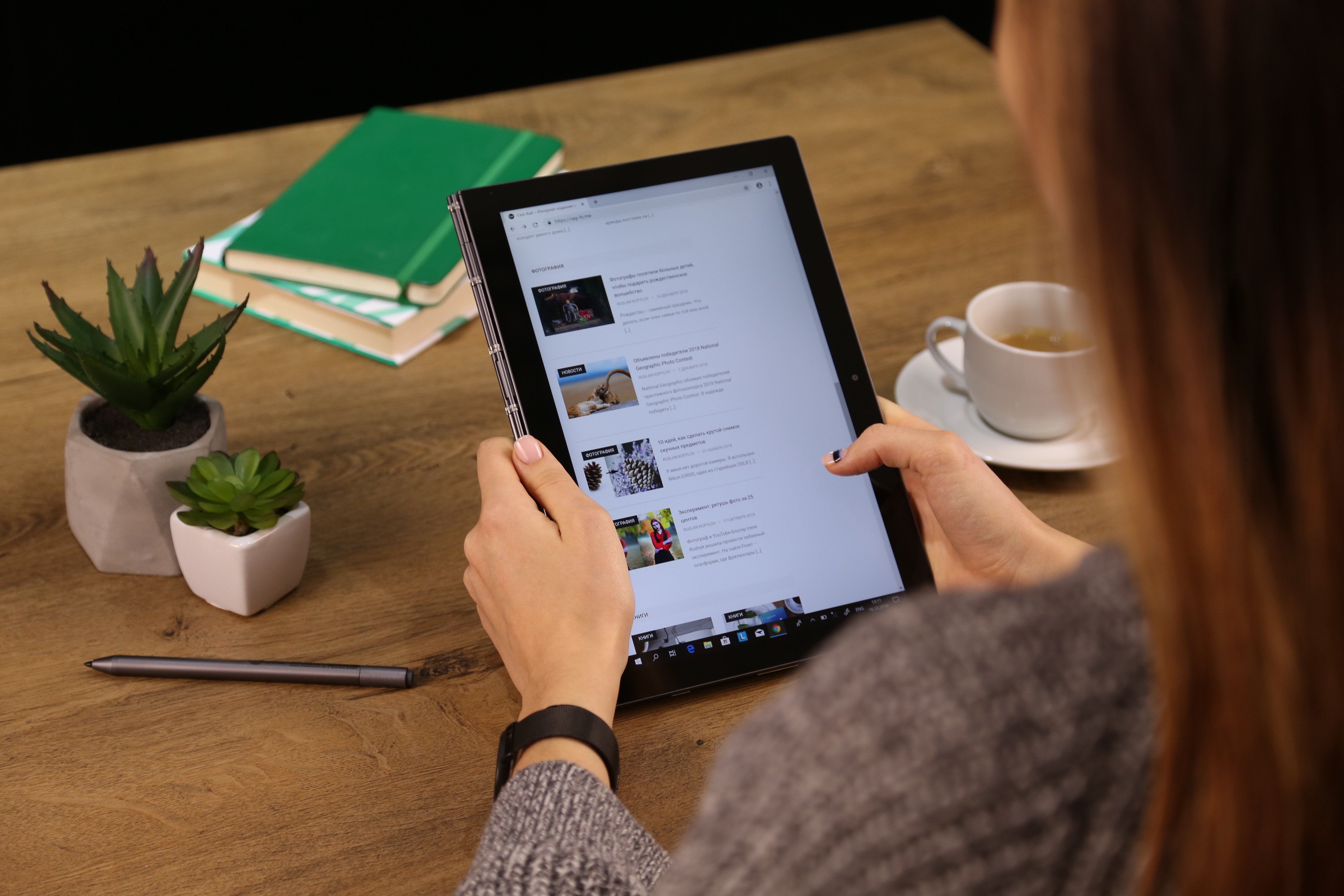 woman scrolling on tablet at desk